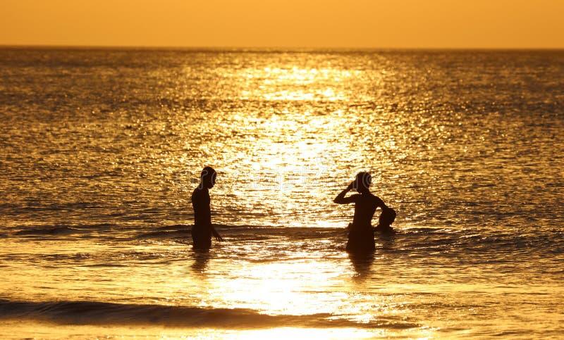 使用在与渔夫小船的海滩的孩子在巴厘岛,在日落期间的印度尼西亚在海滩 免版税库存图片