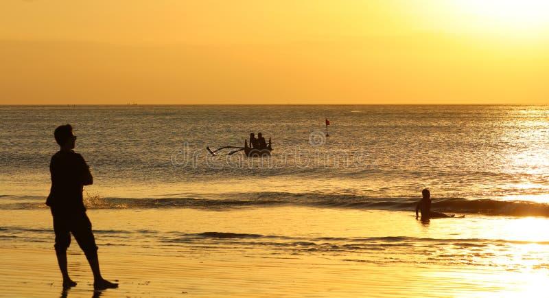 使用在与渔夫小船的海滩的孩子在巴厘岛,在日落期间的印度尼西亚在海滩 免版税图库摄影