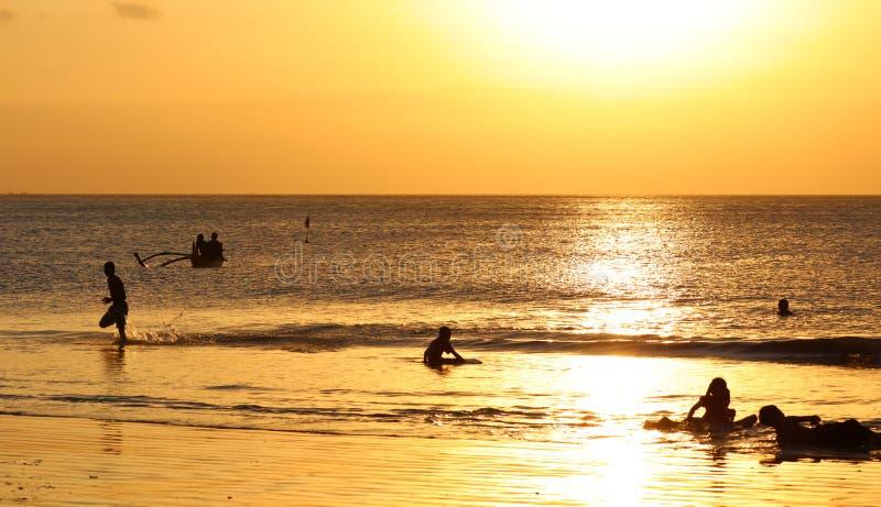 使用在与渔夫小船的海滩的孩子在巴厘岛,在日落期间的印度尼西亚在海滩 免版税库存照片