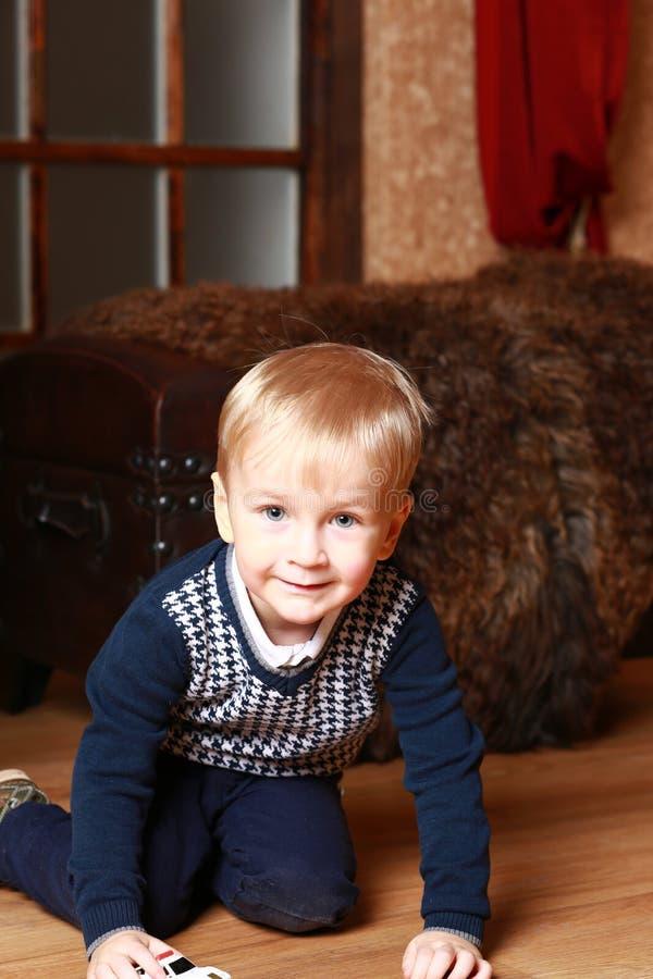 使用在与玩具汽车的地板上的小男孩 库存照片