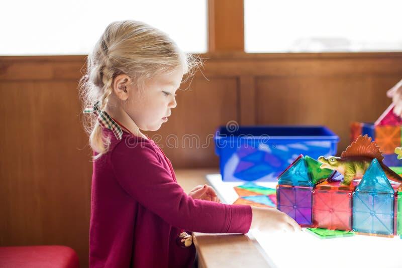 使用在与磁性瓦片的轻的桌上的小女孩 免版税库存照片