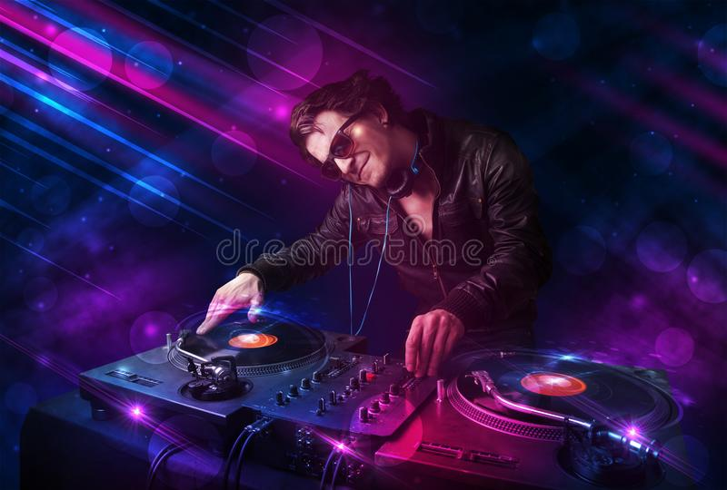 使用在与颜色光线影响的转盘的年轻DJ 免版税库存图片