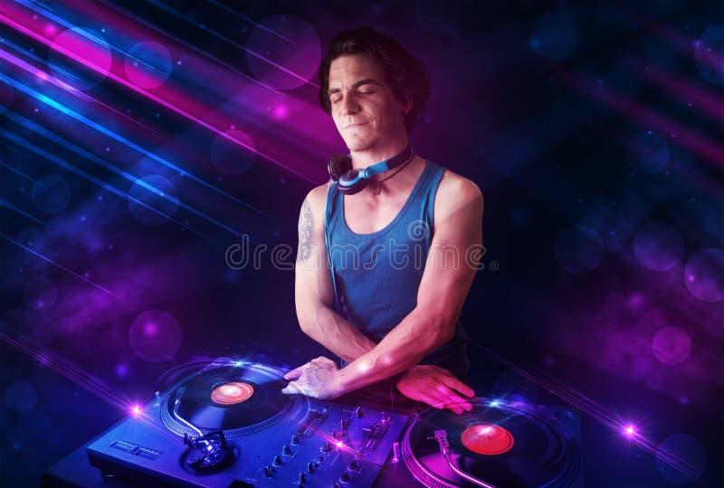 使用在与颜色光线影响的转盘的年轻DJ 库存照片