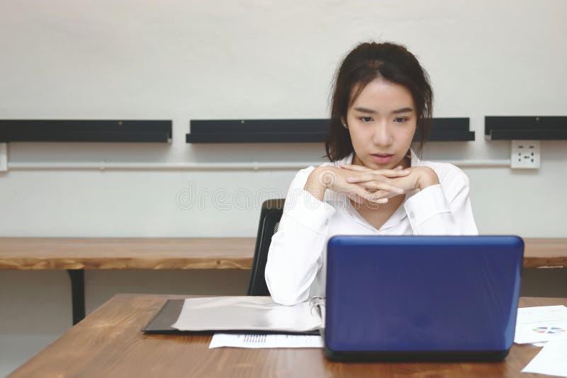 使用在书桌上的可爱的年轻亚裔女商人正面图便携式计算机在办公室 免版税库存照片