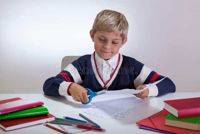使用在书桌上的男孩剪刀 免版税库存照片