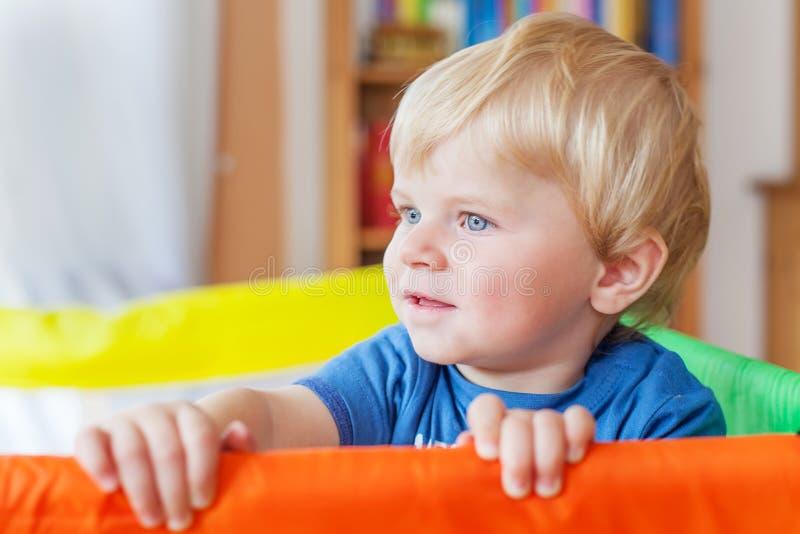 使用在五颜六色的幼儿围栏的逗人喜爱的矮小的男婴,户内 免版税库存图片