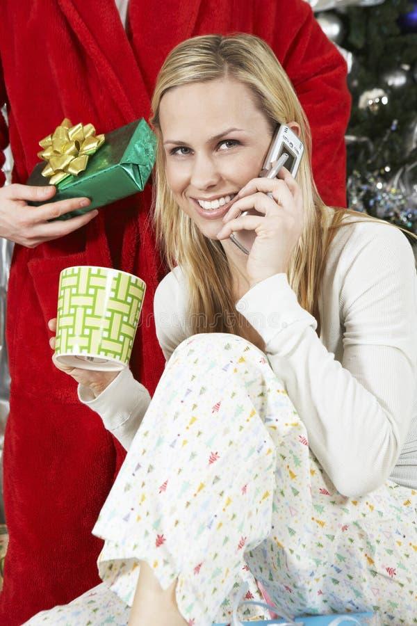 使用在人前面的妇女手机拿着圣诞节礼物 免版税库存图片