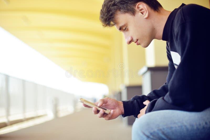 使用在他的智能手机的人流动应用在火车站,旅行 英俊在火车站 微笑自由职业者的人 免版税库存图片