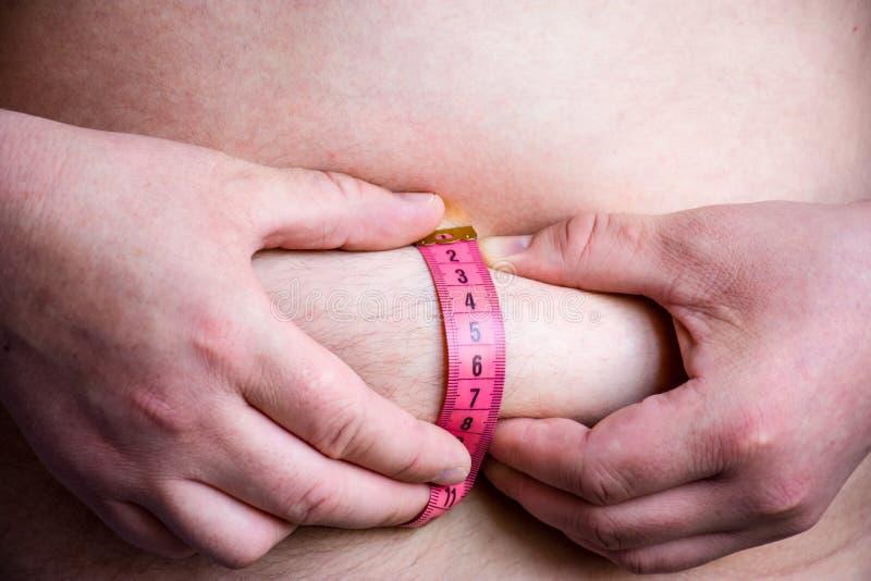使用在他的贝耳的测量的磁带人或患者测量他自己肥胖皮肤折叠的厚度皮肤下油脂出现的  库存图片