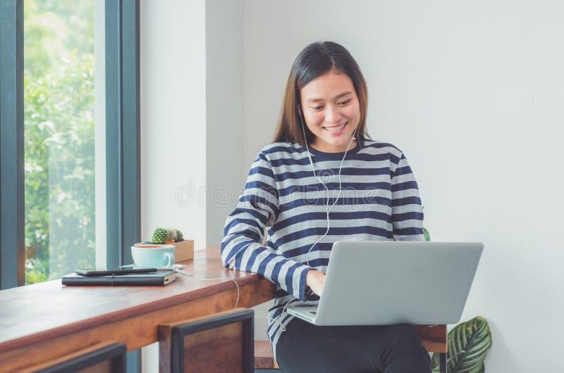 使用在便携式计算机和听的音乐w上的愉快的亚裔妇女 免版税库存图片