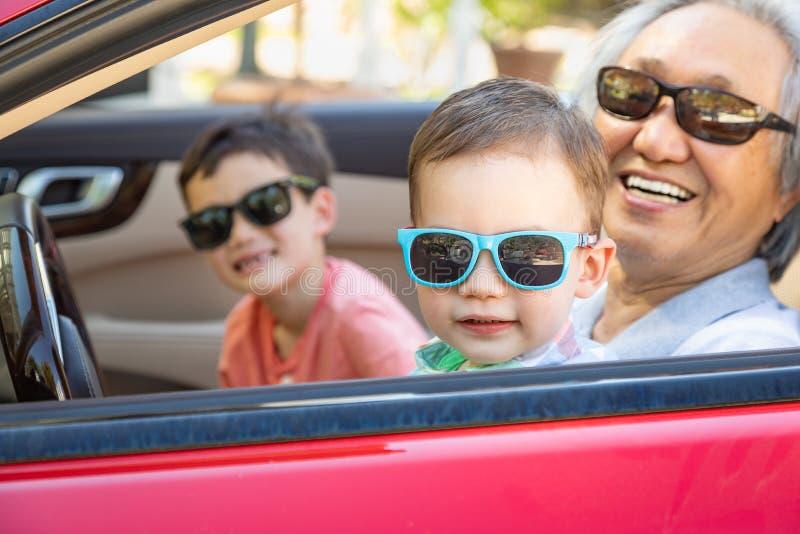 使用在停放的汽车的中国祖父和混合的族种孩子 免版税库存照片