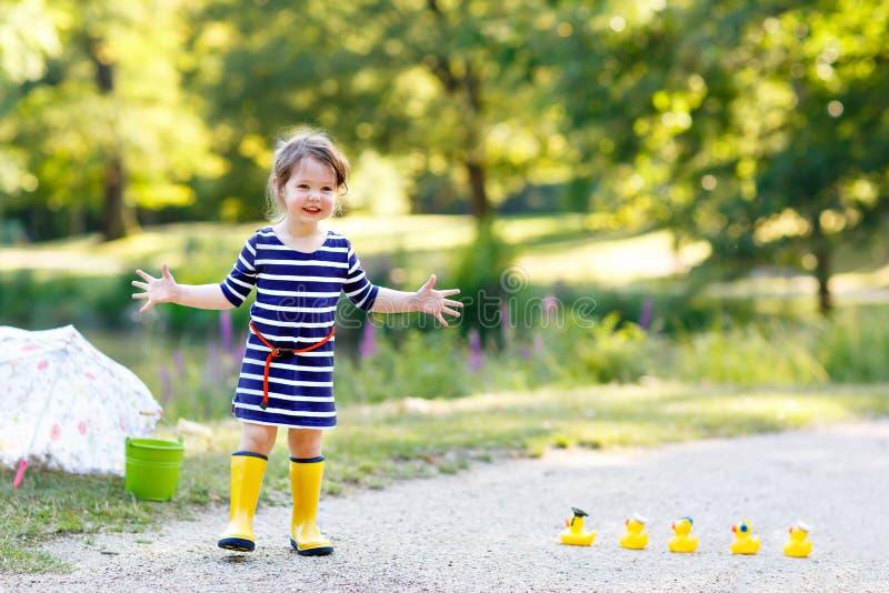使用在公园的美丽的矮小的小孩女孩 可爱的儿童佩带的时尚便衣和黄色胶靴 免版税库存照片