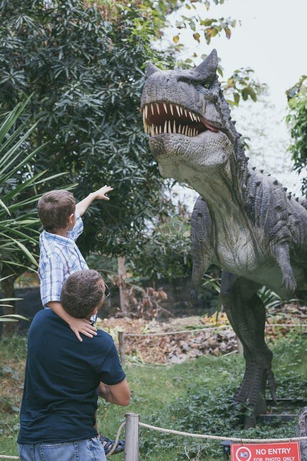 使用在冒险迪诺公园的父亲和儿子 免版税库存照片