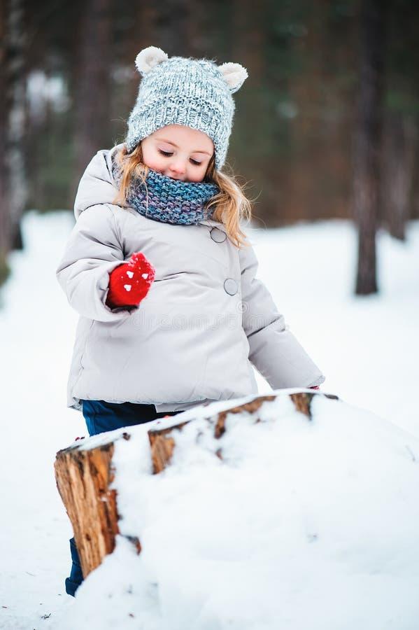 使用在冬天多雪的森林里的逗人喜爱的微笑的女婴 免版税库存照片