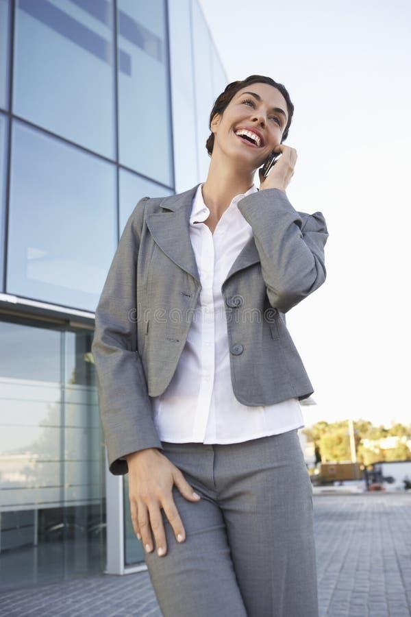 使用在办公楼之外的女实业家手机 免版税库存图片