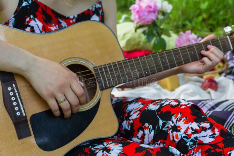 使用在吉他的女孩在公园 免版税库存照片