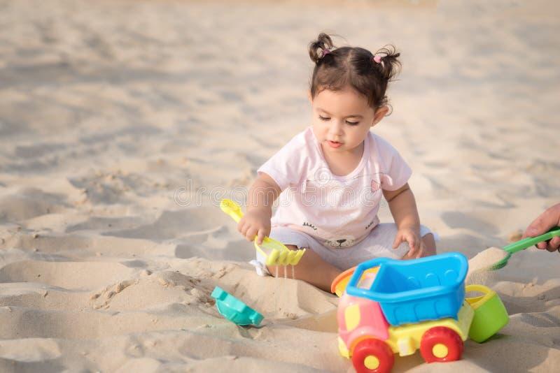 使用在含沙夏天海滩的美丽的甜女婴在海附近 旅行和假期与孩子 库存图片