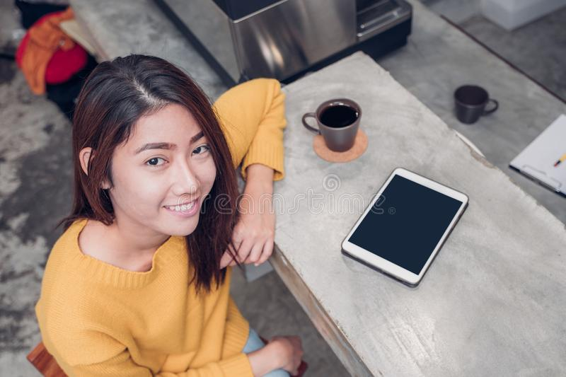 使用在咖啡馆柜台酒吧的亚裔妇女片剂与咖啡杯和 免版税图库摄影