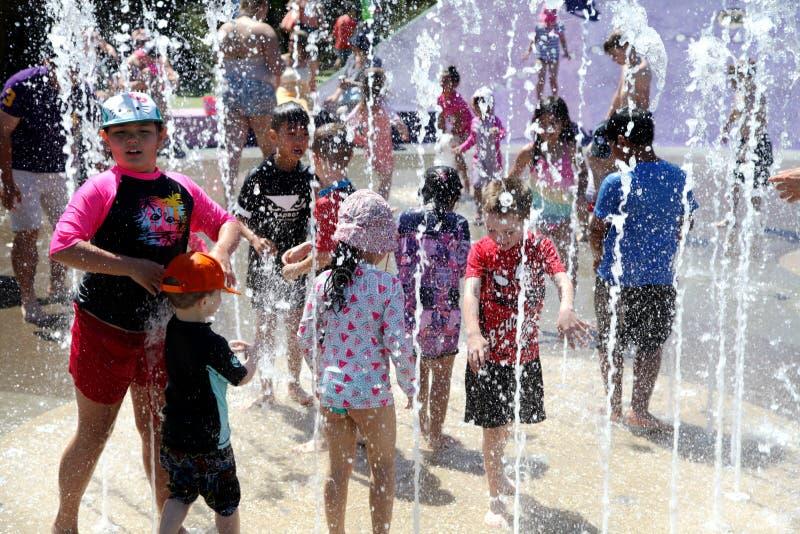 使用在喷泉的孩子在一热的天 库存照片