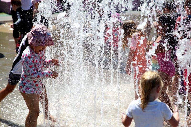使用在喷泉的孩子在一热的天 库存图片