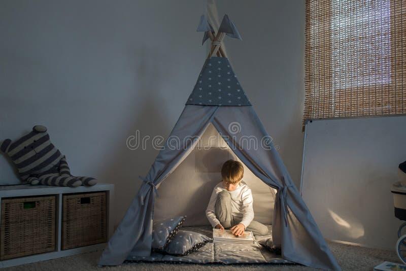 使用在圆锥形帐蓬的男孩 免版税库存图片