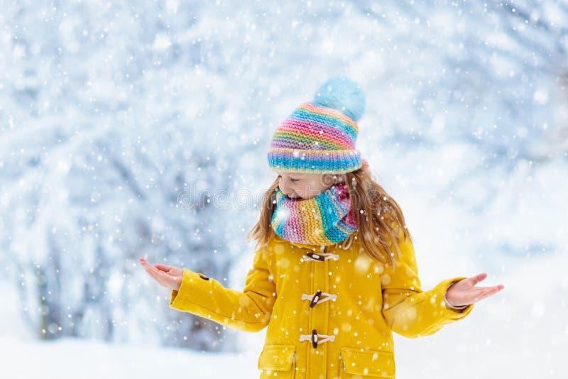 使用在圣诞节的雪的孩子 孩子在冬天 免版税库存图片