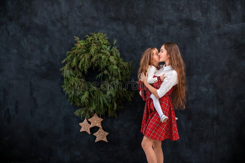 使用在圣诞节花圈附近的母亲和女儿 免版税库存照片