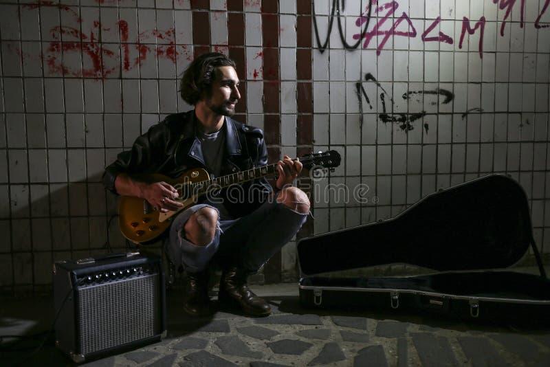 使用在地下过道的吉他的街道音乐家 无业游民的生活方式 在地下过道谋生的使用 失业者 免版税库存图片