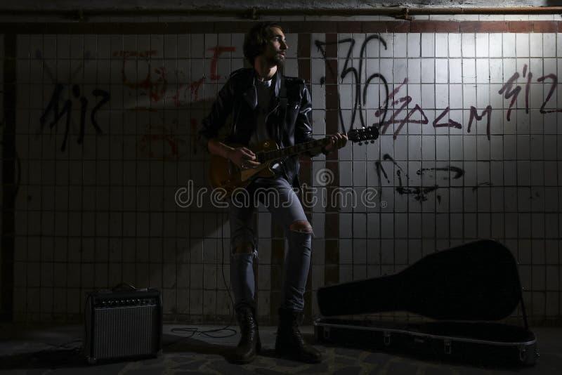使用在地下过道的吉他的街道音乐家 无业游民的生活方式 在地下过道谋生的使用 失业者 图库摄影