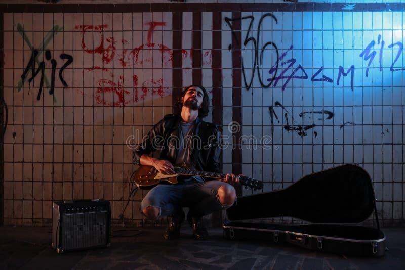 使用在地下过道的吉他的街道音乐家 无业游民的生活方式 在地下过道谋生的使用 失业者 免版税库存照片