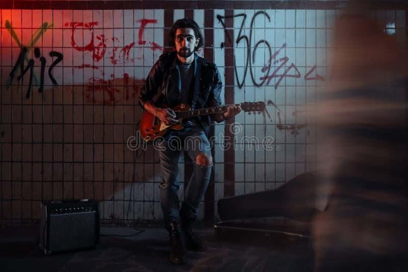 使用在地下过道的吉他的街道音乐家 无业游民的生活方式 在地下过道谋生的使用 失业者 库存图片