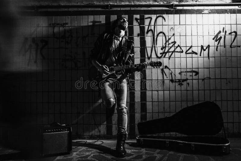 使用在地下过道的吉他的街道音乐家 无业游民的生活方式 在地下过道谋生的使用 失业者 库存照片