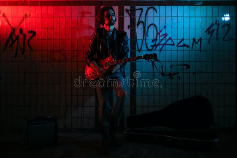 使用在地下过道的吉他的街道音乐家 无业游民的生活方式 在地下过道谋生的使用 失业者 免版税图库摄影