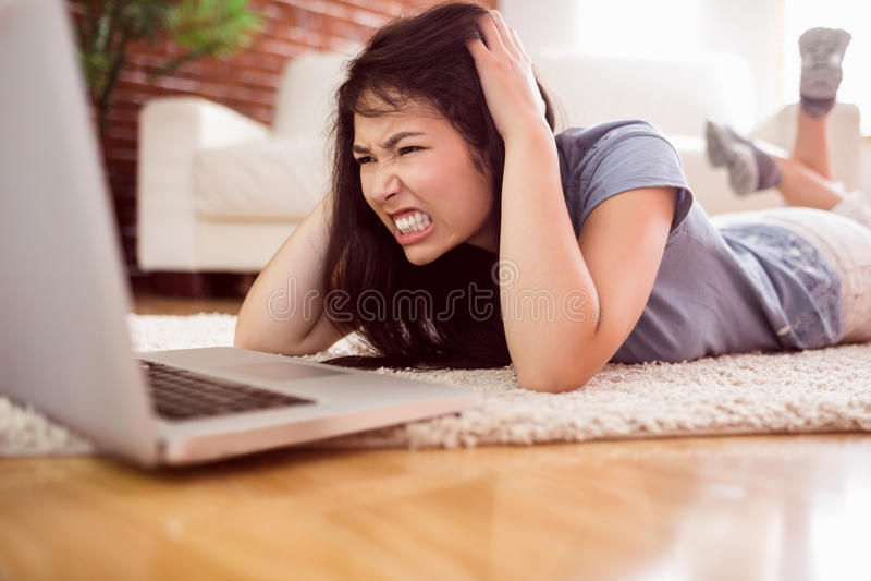 使用在地板上的亚裔恼怒的妇女膝上型计算机 库存照片