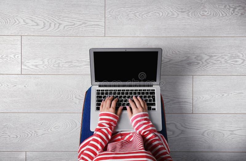 使用在地板,顶视图上的年轻女人膝上型计算机 库存图片