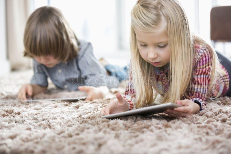 使用在地毯的逗人喜爱的女孩和兄弟数字式片剂在客厅 免版税库存图片