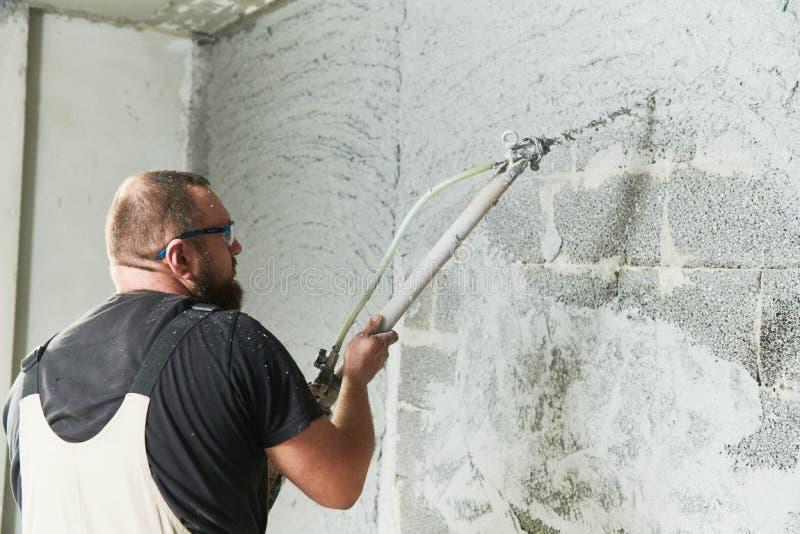 使用在墙壁上的石膏工screeder喷洒的油灰膏药灰浆 免版税库存照片
