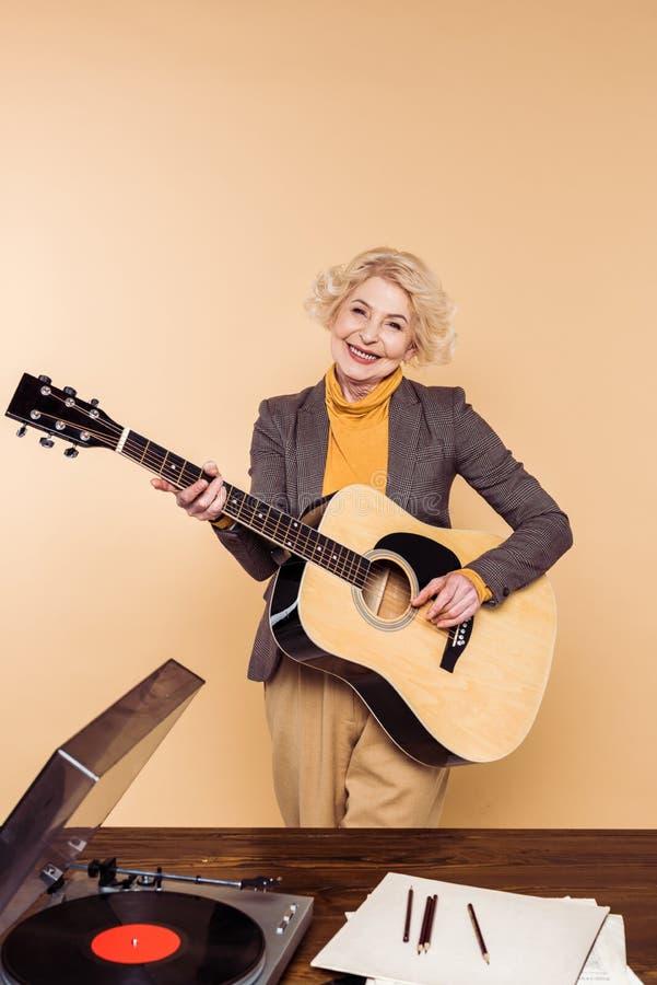 使用在声学吉他的微笑的资深妇女在与唱片的桌附近 免版税库存图片