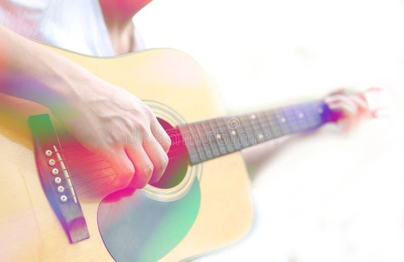 使用在声学吉他的男性手的色的图象 库存照片