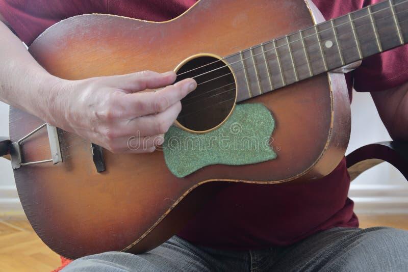 使用在声学吉他的男性手 特写镜头 音乐概念 免版税库存照片