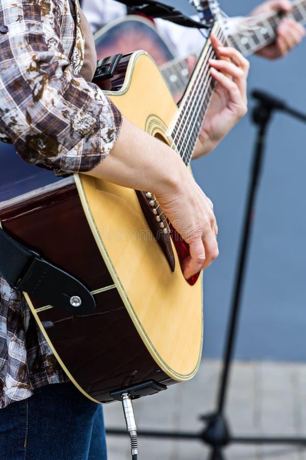 使用在声学吉他的妇女在街道音乐会 图库摄影