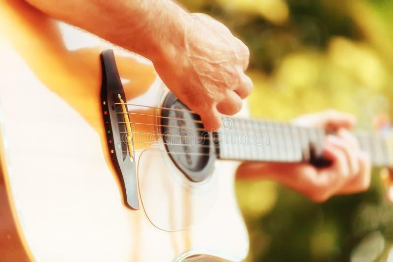 使用在声学吉他的男性手 库存照片