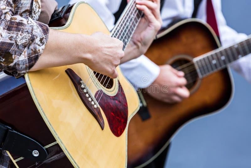 使用在声学吉他的音乐家 图库摄影