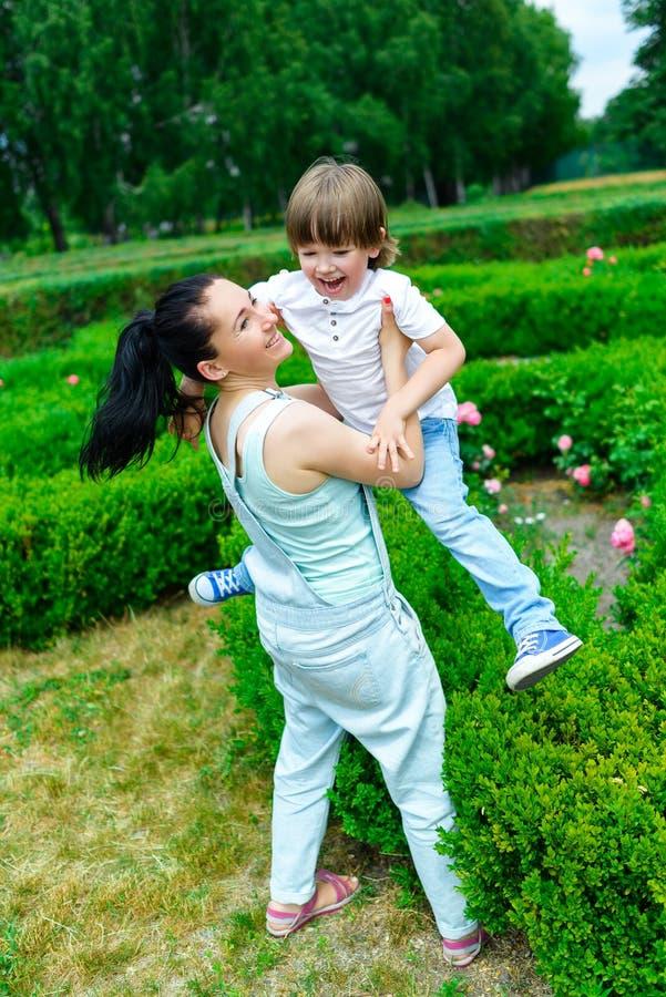 使用在夏天的母亲和愉快的儿子停放 免版税图库摄影
