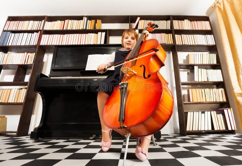 使用在大提琴的一致的礼服的一个小女孩 图库摄影
