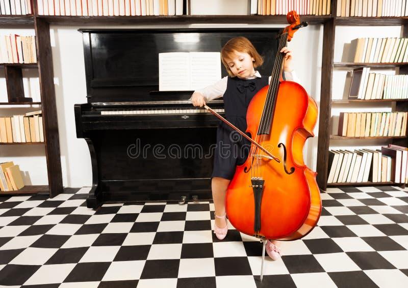 使用在大提琴的学校礼服的美丽的女孩 免版税库存图片