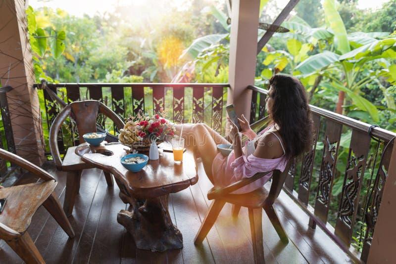 使用在大阳台的少妇细胞巧妙的电话看热带庭院在享用森林的早晨美丽的女孩 免版税图库摄影