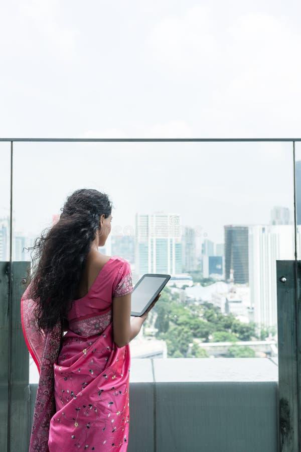 使用在大阳台的年轻印地安妇女一台片剂个人计算机在一个大风天 库存图片