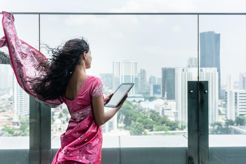 使用在大阳台的年轻印地安妇女一台片剂个人计算机在一个大风天 免版税图库摄影