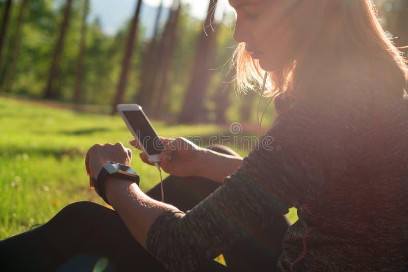 使用在她巧妙的手表的美丽的年轻女运动员健身app监测锻炼表现 生活方式便携的技术 免版税库存图片